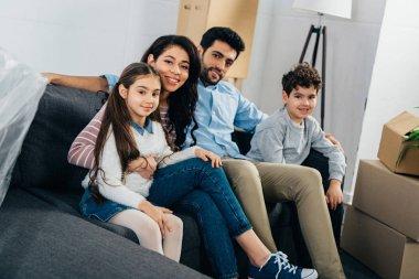 happy hispanic family sitting on sofa in new home