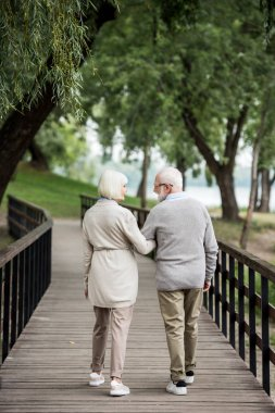 senior couple talking while walking across wooden bridge in park