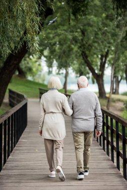 senior couple walking across wooden bridge in park