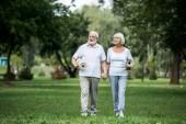 šťastný pár vysokých procházky v parku a držení fitness rohože
