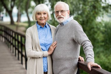 selective focus of nice smiling senior couple standing on wooden bridge in park