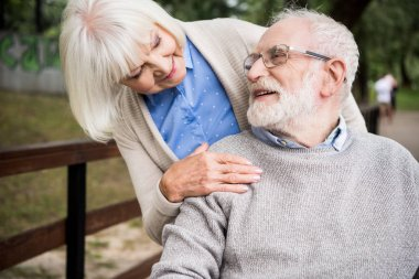 smiling senior woman looking at happy husband in wheelchair, while holding hand on his shoulder