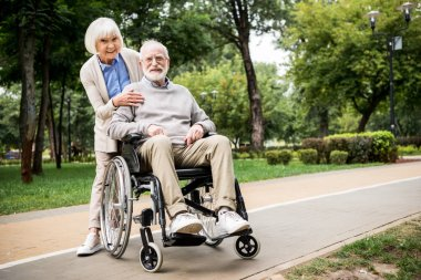 happy senior couple, smiling woman with husband in wheelchair in park