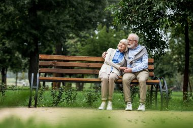 smiling senior couple embracing and holding hands while resting on wooden bench in park