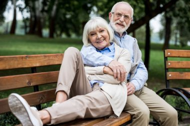 happy senior couple resting on wooden bunch in park