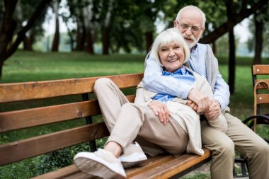 happy senior woman laying on wooden bunch near smiling husband in park