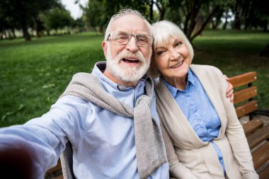 selective focus of happy smiling senior couple sitting on wooden bench in park