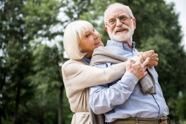 happy senior couple hugging and smiling in park
