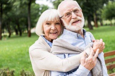 Happy senior woman hugging smiling husband in park stock vector