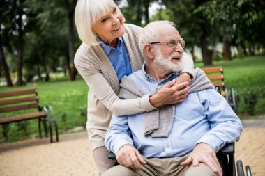 happy senior woman with smiling husband in wheelchair in park