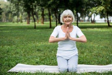 senior woman on yoga mat in meditation sukhasana sitting pose with folded hands