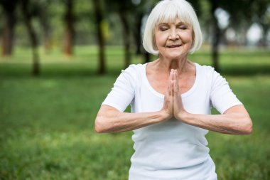 senior woman in meditation sukhasana pose with folded hands