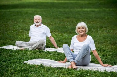 happy senior couple sitting in relaxation poses on yoga mats on green lawn
