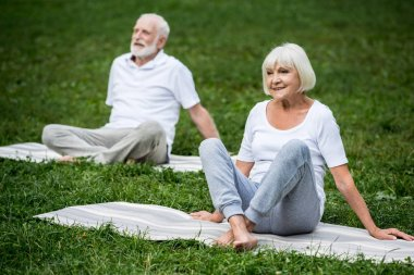 senior couple meditating in relaxation poses while sitting on yoga mats