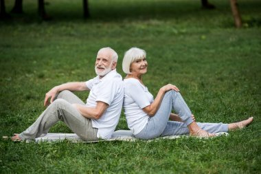 happy senior couple resting on yoga mats on green lawn in park