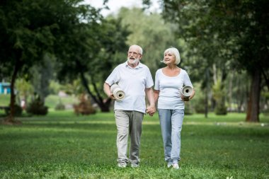 happy senior couple walking in park and holding fitness mats