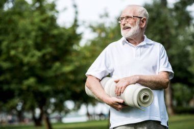 happy senior man with fitness mat in park