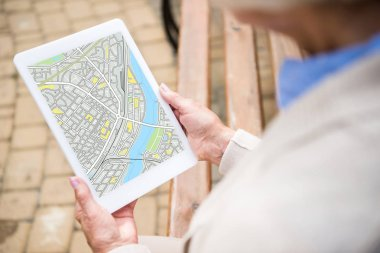 selective focus of senior woman holding digital tablet with map on screen