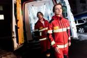 Fotografia Paramedics in red uniform standing near ambulance car