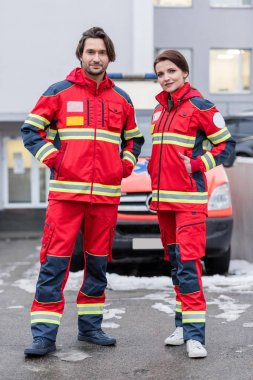 Full length view of paramedics in red uniform standing with hands in pockets