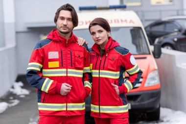 Tired paramedics in red uniform standing in front of ambulance car