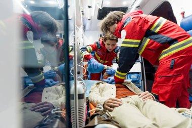 Paramedics doing cardiopulmonary resuscitation in ambulance car