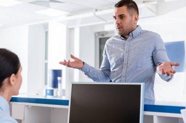 Surprised man talking to nurse in clinic