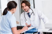 Serious doctor with stethoscope talking to nurse in clinic