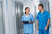 Ärzte mit Zwischenablage und Stethoskop sprechen und einander betrachtend