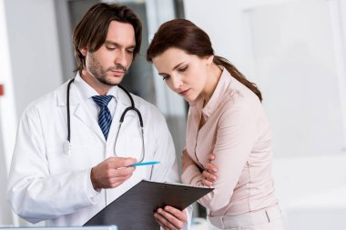 Doctor with stethoscope and patient looking at clipboard