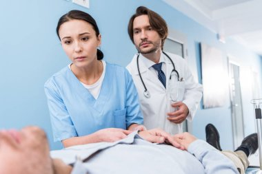 Worried doctors with stethoscope looking at patient