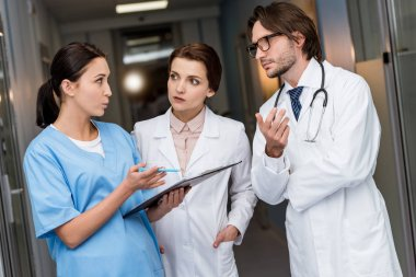 Doctors and nurse with clipboard discussing diagnosis