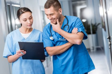 Smiling doctors in blue uniform discussing diagnosis
