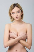 attractive naked young woman covering breast, isolated on grey