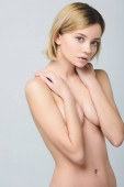 attractive blonde naked woman posing isolated on grey
