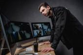 Fotografia concentrati guardia in uniforme guardando monitor del computer allarea di lavoro