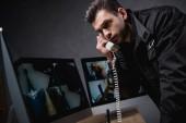 őr egységes beszél a telefonon, és látszó-on számítógép-monitor