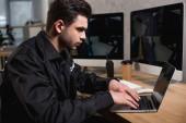 Fotografia premurosa guardia in uniforme utilizzando il computer portatile sul posto di lavoro