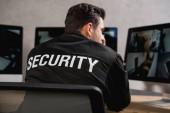Fotografia vista posteriore della guardia nera uniforme guardando a monitor del computer