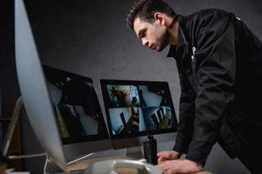 focused guard in uniform looking at computer monitor at workplace