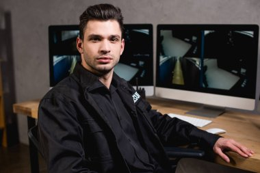 Handsome guard in black uniform looking at camera stock vector