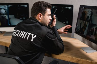 back view of guard in uniform using walkie-talkie