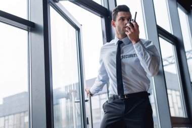 Handsome guard in suit talking on walkie-talkie stock vector
