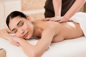 oříznutý pohled masér dělá masáž zad pro krásné asijské ženy