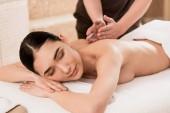 Selektivní fokus masér dělá masáž zad pro krásné asijské ženy