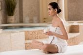 krásná asijská žena v ručníku posezení s šálkem kávy v lázních