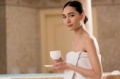 krásná asijská žena v ručníku a při pohledu na fotoaparát s šálek kávy