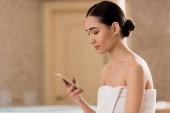 Fotografia donna attraente in tovagliolo usando smartphone presso spa con lo spazio della copia