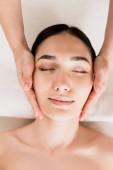 krásná asijská žena dostává masáž obličeje se zavřenýma očima v lázních