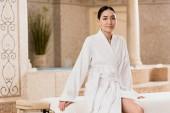 krásná asijská žena v županu, posezení a pohledu kamery